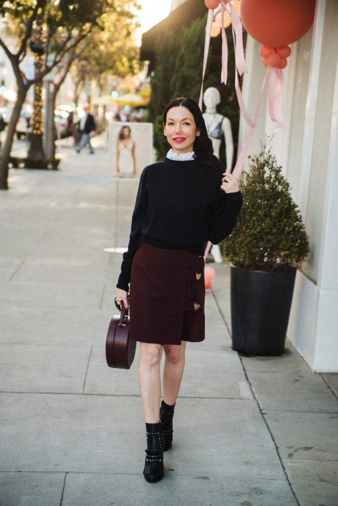 How to Dress Like a Parisian Girl, styling tips featured by top LA fashion blog, Pretty Little Shoppers: image of a woman wearing a Sandro sweater, Storets mini skirt, Tammy & Benjamin bag, Tommy Hilfiger ankle boots, and Oliver Peoples sunglasses.