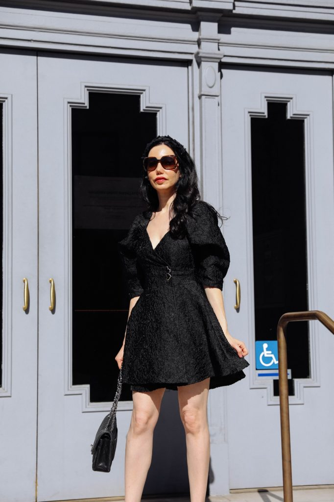 Sister Jane, Little Black Dress, Gucci Sunglasses, Spring Style, What to wear in the Spring, Seasonal Style, What to wear, Ladylike style, Los Angeles Fashion Blogger, Personal Style, Outfit Inspiration, OOTD Inspo, street style stalking, Preppy Style, Parisian Chic, Classic and Feminine, How to style a little black dress #dreamsisterjane #Springstyle #ootd #sisterjane | Sister Jane by popular LA fashion blog, Pretty Little Shoppers: image of a woman standing outside an wearing a Sister Jane black puff sleeve dress, Neiman Marcus pumps, Tarina Tarantino headband, Gucci 58MM Oversized Square Sunglasses, and holding a CHANEL PRE-OWNED Double Flap quilted shoulder bag.