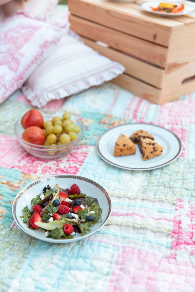 Summer Salad with Berries and Goat Cheese | Virtual Picnic by popular L.A. lifestyle blog, Pretty Little Shoppers: image of a bowl of fruit, gluten-free chocolate chip scones, and fruit salad on a patchwork quilt.