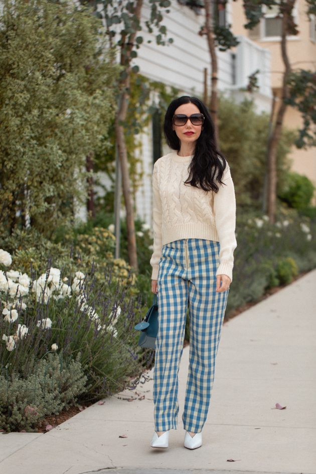How to Wear Gingham for Fall, What to wear Fall 2020, Fall Transitional Look, Capulet Gingham Pants, White Cable knit Sweater, Joseph and Stacey Bag, Los Angeles Fashion Blogger, Pretty Little Shoppers Blog #Gingham #GinghamStyle | Fall Clothing by popular L.A. fashion blog, Pretty Little Shoppers: image of a woman walking down a sidewalk and wearing a pair of Capulet gingham pants, J.O.A sweater, Aqua mules and carrying a Joseph and Stacey bag.