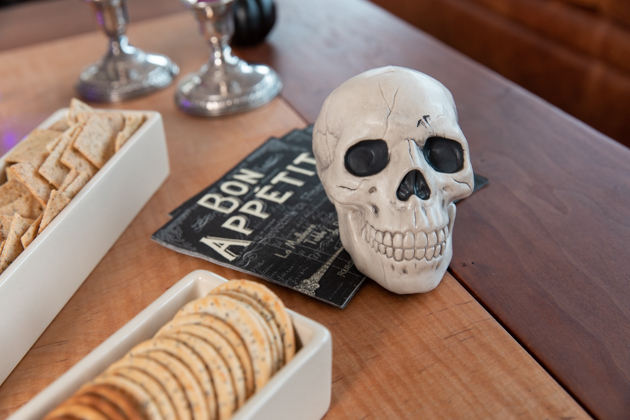 Halloween Cheese Platter and Candy Buffet, Celebrating Halloween In My New House, Halloween Ideas, How to Celebrate Halloween at Home, Halloween Ideas during Covid-19 Quarantine, Los Angeles Lifestyle Blogger, Pretty Little Shoppers Blog, Halloween Decorations #Halloween2020 #HalloweenCheesePlatter |Cheese Platter by popular LA lifestyle blog, Pretty Little Shoppers: image of a skull decoration next to two white ceramic dishes filled with crackers.