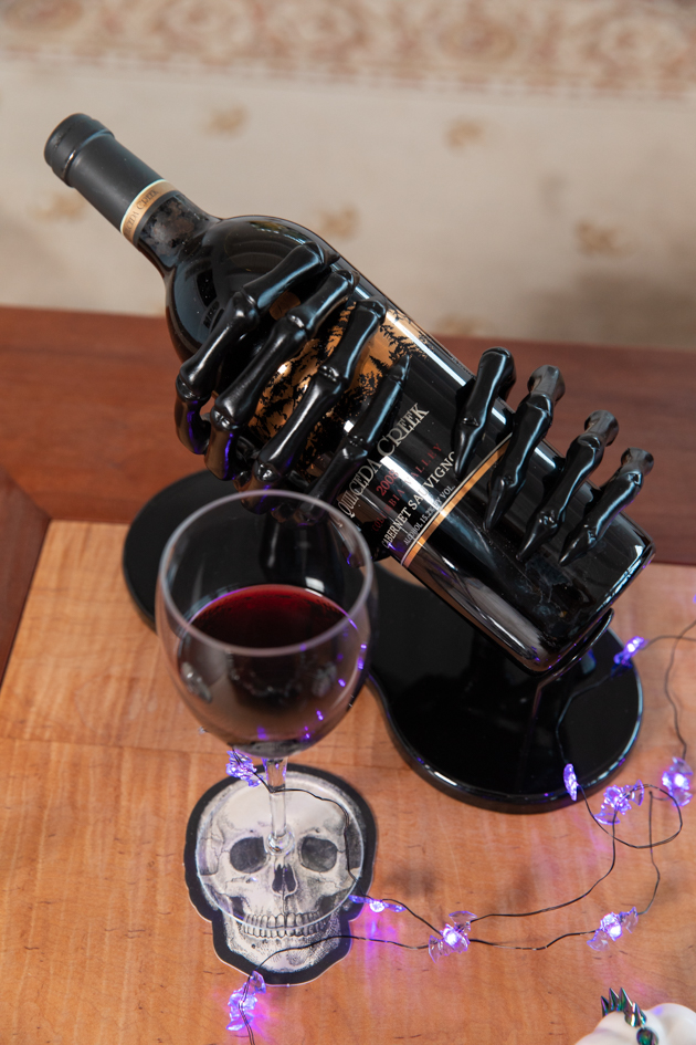 Skeleton Hands Wine Holder |Cheese Platter by popular LA lifestyle blog, Pretty Little Shoppers: image of a glass of red wine next to a bottle of red wine in a black skeleton hands wine holder.