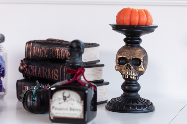 Celebrating Halloween In My New House, Halloween Ideas, How to Celebrate Halloween at Home, Halloween Ideas during Covid-19 Quarantine, Los Angeles Lifestyle Blogger, Pretty Little Shoppers Blog, Halloween Decorations #Halloween2020 |Cheese Platter by popular LA lifestyle blog, Pretty Little Shoppers: image of potion books, black apothecary jar, and skull stand with pumpkin shaped candle on it.