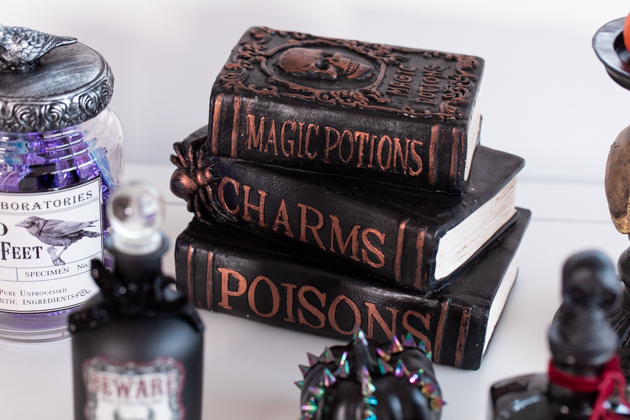 Halloween Spell and Poison Books Decoration |Cheese Platter by popular LA lifestyle blog, Pretty Little Shoppers: image of potion books, apothecary jars and a black pumpkin.
