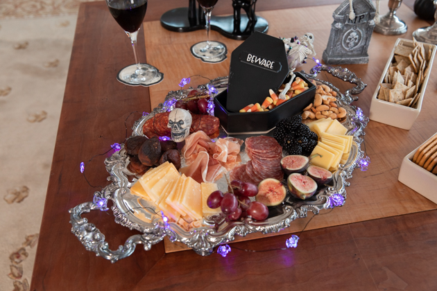 Halloween Cheese Platter and Candy Buffet, Celebrating Halloween In My New House, Halloween Ideas, How to Celebrate Halloween at Home, Halloween Ideas during Covid-19 Quarantine, Los Angeles Lifestyle Blogger, Pretty Little Shoppers Blog, Halloween Decorations #Halloween2020 #HalloweenCheesePlatter |Cheese Platter by popular LA lifestyle blog, Pretty Little Shoppers: image of a meat and cheese platter with a coffin shaped candy dish next to some glasses of red wine.