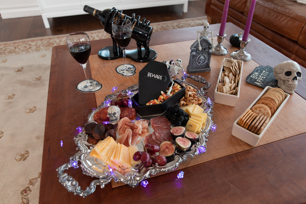 Halloween Cheese Platter and Candy Buffet, Celebrating Halloween In My New House, Halloween Ideas, How to Celebrate Halloween at Home, Halloween Ideas during Covid-19 Quarantine, Los Angeles Lifestyle Blogger, Pretty Little Shoppers Blog, Halloween Decorations #Halloween2020 #HalloweenCheesePlatter |Cheese Platter by popular LA lifestyle blog, Pretty Little Shoppers: image of a meat and cheese platter with a coffin shaped candy dish next to some purple candle sticks in silver candle stick holder and a black skeleton hands wine holder.