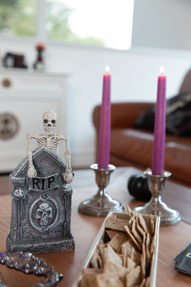 Celebrating Halloween In My New House, Halloween Ideas, How to Celebrate Halloween at Home, Halloween Ideas during Covid-19 Quarantine, Los Angeles Lifestyle Blogger, Pretty Little Shoppers Blog, Halloween Decorations #Halloween2020 |Cheese Platter by popular LA lifestyle blog, Pretty Little Shoppers: image of purple candle sticks in silver candle stick holders, skeleton and tombstone decor and a dish filled with crackers.