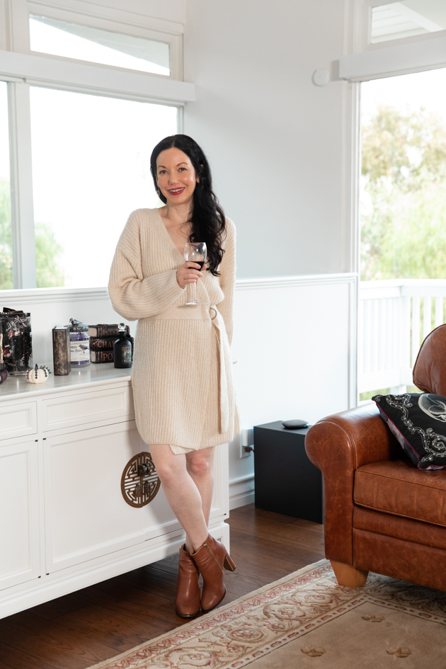 Celebrating Halloween In My New House, Halloween Ideas, How to Celebrate Halloween at Home, Halloween Ideas during Covid-19 Quarantine, Los Angeles Lifestyle Blogger, Pretty Little Shoppers Blog, Halloween Decorations #Halloween2020 #HalloweenCheesePlatter #FallFashion2020 #SweaterDress Dressing Up at Home during Covid-19 Quarantine, Lisa Valerie Morgan, Sweater Dress with Ankle Boots  Cheese Platter by popular LA lifestyle blog, Pretty Little Shoppers: image of a woman wearing a beige wrap sweater dress with brown ankle boots and leaning up against a white dresser decorated with Halloween decor while holding a glass of red wine.