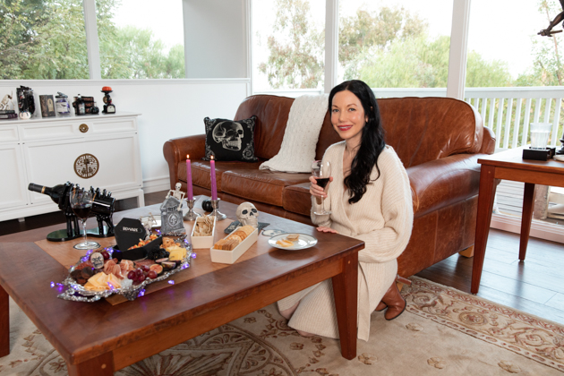 Halloween Cheese Platter and Candy Buffet, Celebrating Halloween In My New House, Halloween Ideas, How to Celebrate Halloween at Home, Halloween Ideas during Covid-19 Quarantine, Los Angeles Lifestyle Blogger, Pretty Little Shoppers Blog, Halloween Decorations #Halloween2020 #HalloweenCheesePlatter #FallFashion2020 #SweaterDress Dressing Up at Home during Covid-19 Quarantine, Lisa Valerie Morgan, Sweater Dress with Ankle Boots |Cheese Platter by popular LA lifestyle blog, Pretty Little Shoppers: image of a woman kneeling on the ground next to a coffee table set with a cheese plater, crackers, and red wine in a black skeleton hands wine holder.