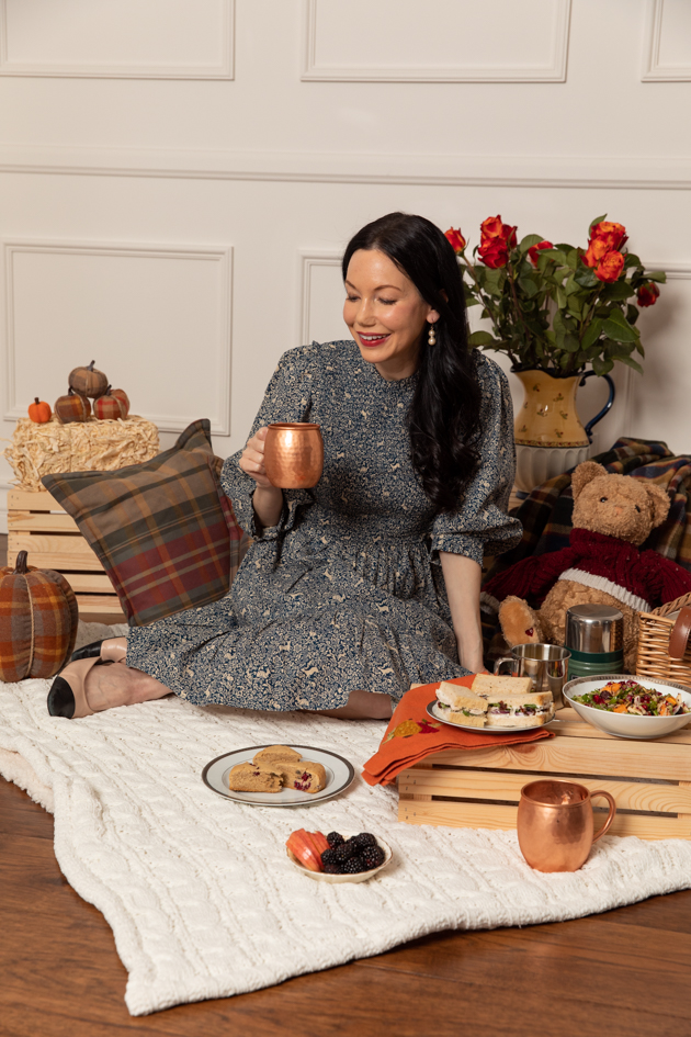 Indoor Fall Picnic, Fall Harvest Picnic Menu, Doen Fawn Dress, Lisa Valerie Morgan, Pretty Little Shoppers Blog, Los Angeles Lifestyle Blogger, How to Celebrate Thanksgiving During Quarantine, Holiday Ideas During Covid Quarantine #IndoorPicnic #ThanksgivingIdeas |Fall Picnic by popular LA lifestyle blog, Pretty Little Shoppers: image of a woman sitting on a knit cream blanket and having an indoor picnic.