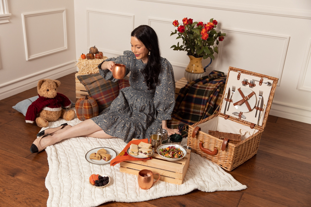 Indoor Fall Picnic, Fall Harvest Picnic Menu, Doen Fawn Dress, Lisa Valerie Morgan, Pretty Little Shoppers Blog, Los Angeles Lifestyle Blogger, How to Celebrate Thanksgiving During Quarantine, Holiday Ideas During Covid Quarantine #IndoorPicnic #ThanksgivingIdeas | Fall Picnic by popular LA lifestyle blog, Pretty Little Shoppers: image of a woman sitting on a knit cream blanket and having an indoor picnic.