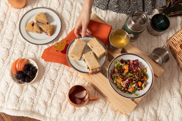 Thanksgiving Inspired Fall Harvest Picnic Menu |Fall Picnic by popular LA lifestyle blog, Pretty Little Shoppers: image of a bowl of fruit, cranberry scones, thermos of soup, sandwiches, salad, and a copper mug filled with water.