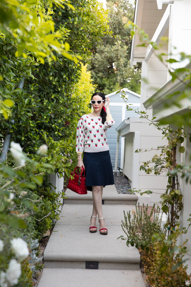 Fall Transitional Look, Waiting for Election Results, Red White and Blue Outfit, LoveShackFancy Strawberry Sweater, Tommy Hilfiger Collection Skirt, Italic Cateye Sunglasses, Lady Dior Bag, Classic and Feminine Style, What to Wear for Fall, Fall in Los Angeles, Preppy Style Los Angeles Lifestyle Blogger, Pretty Little Shoppers Blog #FallTransitionalLook #PreppyStyle |Fall Clothing by popular L.A. fashion blog, Pretty Little Shoppers: image of a woman wearing a strawberry Net-A-Porter sweater, Dior purse, Tommy Hilfiger skirt, plaid block heel sandals, and Italic sunglasses.