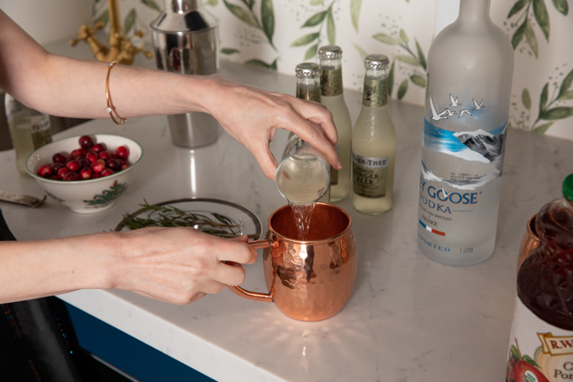 Holiday Moscow Mule, Christmas Cocktail Ideas, Thanksgiving Cocktail Ideas, Festive Holiday Drinks, Home Bar, Home Interior, How to Celebrate the Holidays at Home, Holiday Ideas During Covid Quarantine, Yule Mule, Holiday Moscow Mocktail Los Angeles Lifestyle Blogger, Pretty Little Shoppers Blog #holidaymoscowmule #yulemule #holidaymoscowmocktail | Moscow Mule Recipe by popular LA lifestyle blog, Pretty Little Shoppers: image of a woman pouring some ginger beer into a copper mug.