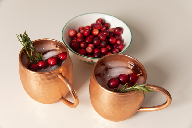 Holiday Moscow Mule, Christmas Cocktail Ideas, Thanksgiving Cocktail Ideas, Festive Holiday Drinks, Home Bar, Home Interior, How to Celebrate the Holidays at Home, Holiday Ideas During Covid Quarantine, Yule Mule, Holiday Moscow Mocktail Los Angeles Lifestyle Blogger, Pretty Little Shoppers Blog #holidaymoscowmule #yulemule #holidaymoscowmocktail |Moscow Mule Recipe by popular LA lifestyle blog, Pretty Little Shoppers: image of two Moscow Mules in copper mugs next to a bowl of cranberries.