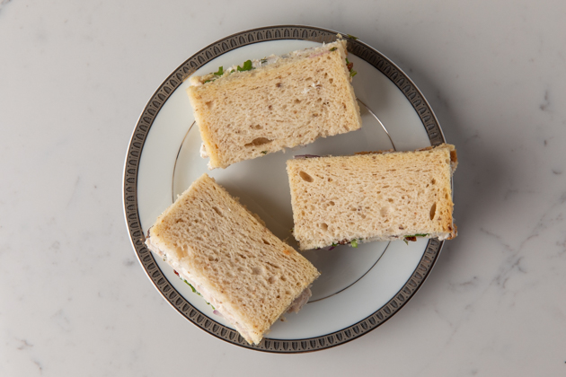 Gluten and Dairy-free Turkey and Cranberry Tea Sandwiches |Turkey Cranberry Sandwich by popular LA lifestyle blog, Pretty Little Shoppers: image of some gluten and dairy free turkey cranberry sandwiches on a white plate.