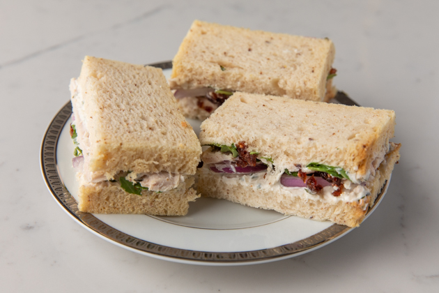 Gluten-free Sandwich Ideas for a Holiday High Tea Party |Turkey Cranberry Sandwich by popular LA lifestyle blog, Pretty Little Shoppers: image of some gluten and dairy free turkey cranberry sandwiches on a white plate.
