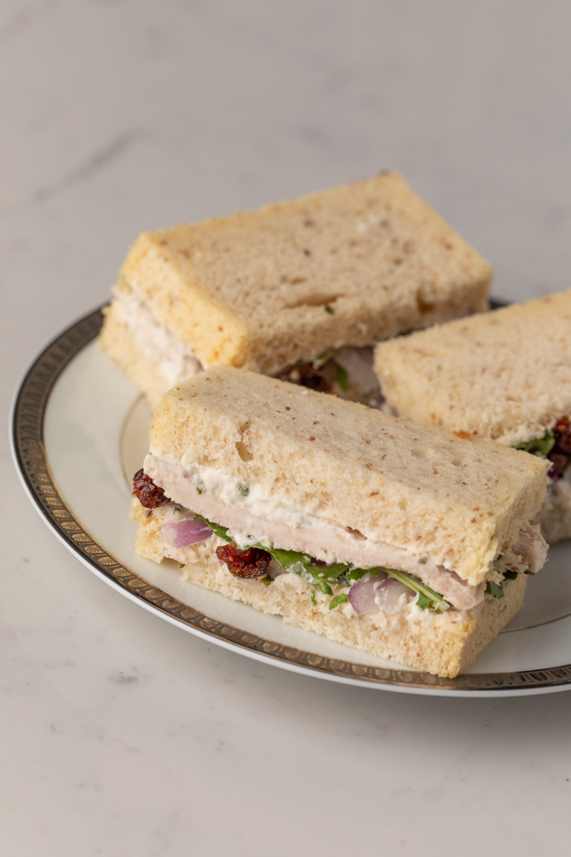Gluten and Dairy-free Turkey and Cranberry Tea Sandwiches, Kite Hill Chive Almond Milk Cream Cheese Spread, Tea Party Sandwiches, Gluten and Dairy Free High Tea Menu, Holiday Party Ideas, Pretty Little Shoppers Blog, Los Angeles Lifestyle Blogger | Turkey Cranberry Sandwich by popular LA lifestyle blog, Pretty Little Shoppers: image of some gluten and dairy free turkey cranberry sandwiches on a white plate.