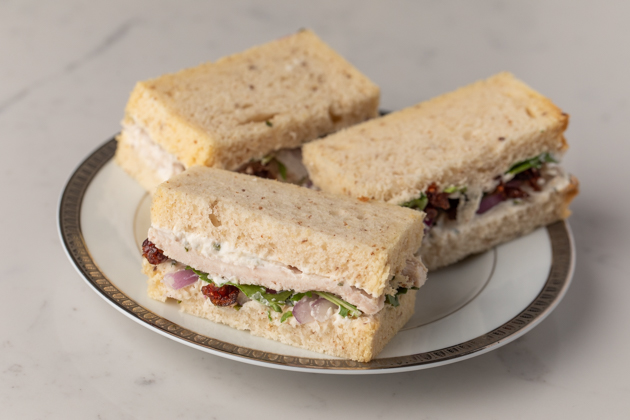 Gluten and Dairy-free Turkey and Cranberry Tea Sandwiches, Kite Hill Chive Almond Milk Cream Cheese Spread, Tea Party Sandwiches, Gluten and Dairy Free High Tea Menu, Holiday Party Ideas, Pretty Little Shoppers Blog, Los Angeles Lifestyle Blogger |Turkey Cranberry Sandwich by popular LA lifestyle blog, Pretty Little Shoppers: image of some gluten and dairy free turkey cranberry sandwiches on a white plate.