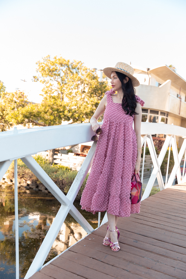 My thoughts on the New Year and a major life update! | Life Update by popular LA lifestyle blog, Pretty Little shoppers: image of a woman wearing a pink dress, straw boater hat, and pink strappy sandals while standing on a bridge.