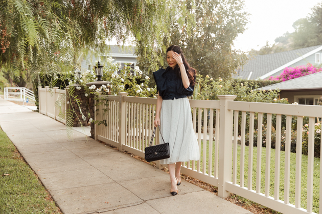 Woman wearing blue statement top and pleated skirt walking on sidewalk |Life Update by popular LA lifestyle blog, Pretty Little Shoppers: image of a woman walking on a sidewalk and wearing a By Abigal Love blue Statement blouse, grey pleated skirt and carrying a Black quilted Chanel bag