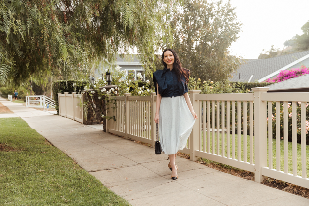 By Abigail Love blue statement blouse with white pleated skirt |Life Update by popular LA lifestyle blog, Pretty Little Shoppers: image of a woman standing next to a white picket fence and wearing a By Abigal Love blue Statement blouse, grey pleated skirt and carrying a Black quilted Chanel bag.