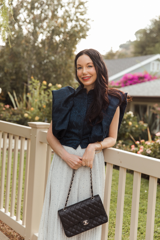 Woman wearing By Abigail Love statement blouse and holding black Chanel bag leaning on white picket fence |Life Update by popular LA lifestyle blog, Pretty Little Shoppers: image of a woman standing next to a white picket fence and wearing a By Abigal Love blue Statement blouse, grey pleated skirt and carrying a Black quilted Chanel bag.