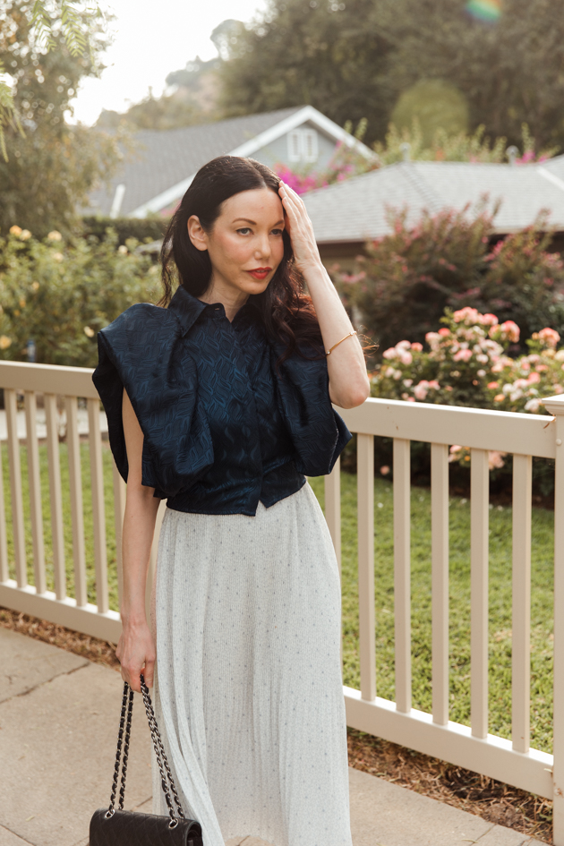 Woman wearing blue statement top on a Spring afternoon |Life Update by popular LA lifestyle blog, Pretty Little Shoppers: image of a woman standing next to a white picket fence and wearing a By Abigal Love blue Statement blouse, grey pleated skirt and carrying a Black quilted Chanel bag.