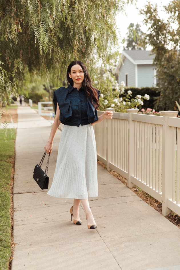 By Abigal Love blue Statement blouse with Black quilted Chanel bag | Life Update by popular LA lifestyle blog, Pretty Little Shoppers: image of a woman wearing a By Abigal Love blue Statement blouse, grey pleated skirt and carrying a Black quilted Chanel bag