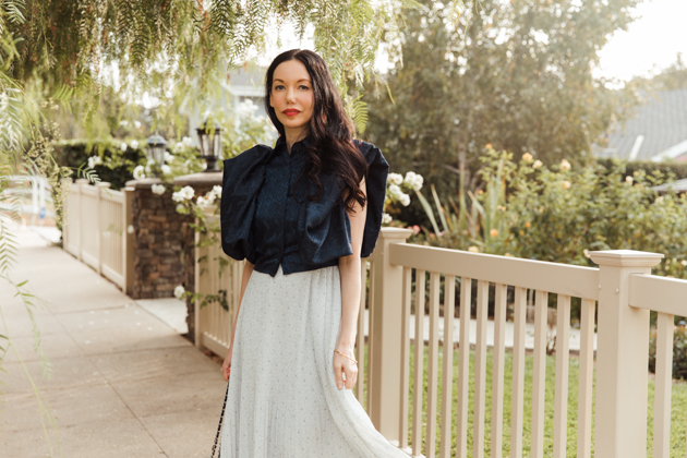 Woman wearing blue top and white pleated skirt stands in front of white picket fence. |Life Update by popular LA lifestyle blog, Pretty Little Shoppers: image of a woman standing next to a white picket fence and wearing a By Abigal Love blue Statement blouse, grey pleated skirt and carrying a Black quilted Chanel bag