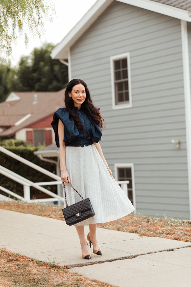 White pleated dress styled with blue statement top |Life Update by popular LA lifestyle blog, Pretty Little Shoppers: image of a woman walking on a sidewalk and wearing a By Abigal Love blue Statement blouse, grey pleated skirt and carrying a Black quilted Chanel bag