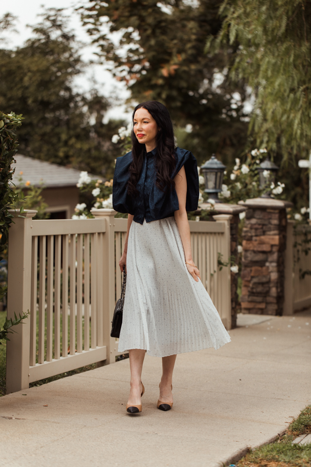 Blue Statement Blouse styled with a pleated skirt for Spring |Life Update by popular LA lifestyle blog, Pretty Little Shoppers: image of a woman standing next to a white picket fence and wearing a By Abigal Love blue Statement blouse, grey pleated skirt and carrying a Black quilted Chanel bag.