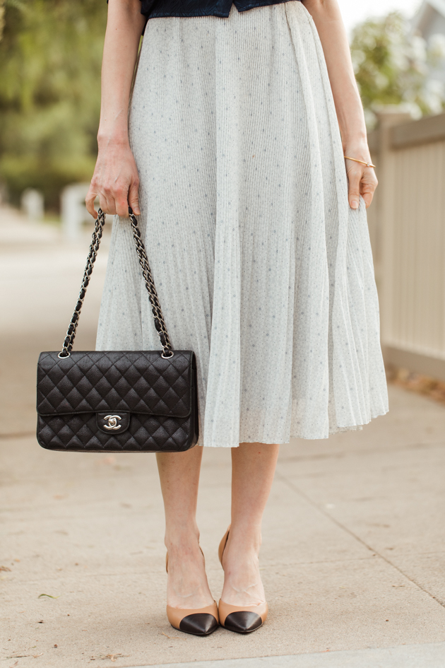 Abercrombie and Fitch pleated dress with black Chanel bag and cap toe pumps |Life Update by popular LA lifestyle blog, Pretty Little Shoppers: image of a woman standing next to a white picket fence and wearing a By Abigal Love blue Statement blouse, grey pleated skirt and carrying a Black quilted Chanel bag.