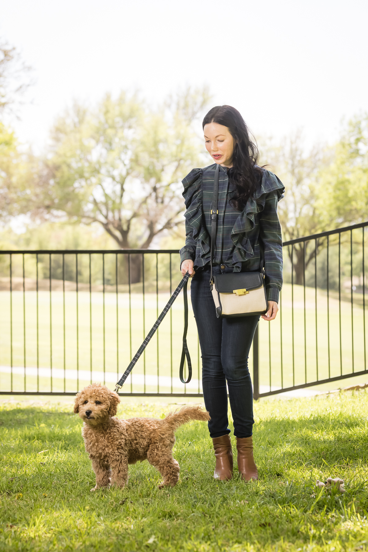 GoldenDoodle Puppy, Matching Mom and Dog Outfits, Tartan Blouse, Tartan Bowtie and Leash, Meet My New Puppy, New Puppy Cuteness, Pretty Little Shoppers Blog, Dallas Lifestyle Blog, #GoldenDoodlePuppy #MeetMyPup |Charlie Cupcake by popular Dallas lifestyle blog, Pretty Little Shoppers: image of a woman wearing a plaid ruffle top and jeans and standing next to her goldendoodle puppy.