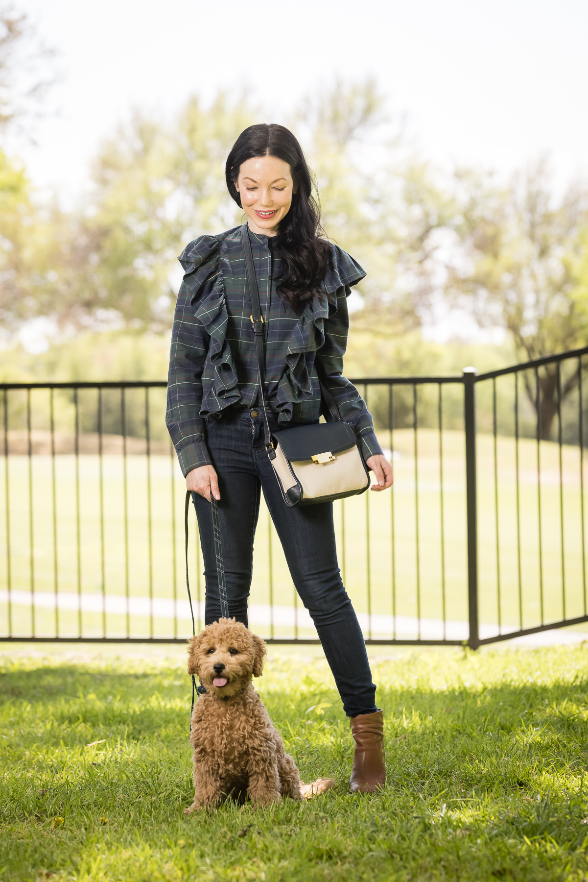 GoldenDoodle Puppy, Tartan Blouse, Tartan Bowtie and Leash, Meet My New Puppy, New Puppy Cuteness, Matching Mom and Dog Outfits, Pretty Little Shoppers Blog, Dallas Lifestyle Blog #GoldenDoodlePuppy #MeetMyPup |Charlie Cupcake by popular Dallas lifestyle blog, Pretty Little Shoppers: image of a woman wearing a plaid ruffle top and jeans and standing next to her goldendoodle puppy.