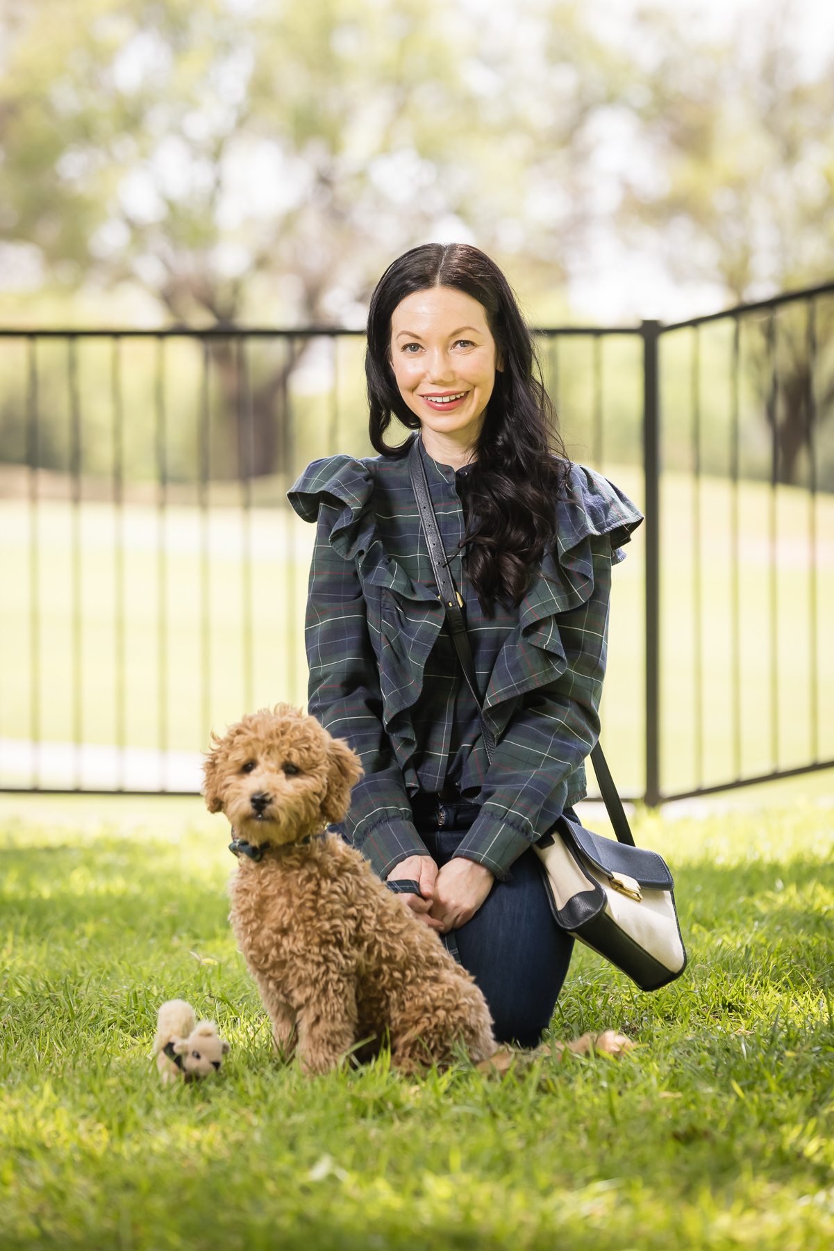 New Puppy, Baby Goldendoodle, Tartan Blouse, Denim, Matching Mom and Puppy outfit | Charlie Cupcake by popular Dallas lifestyle blog, Pretty Little Shoppers: image of a woman wearing a plaid ruffle top and jeans and kneeling next to her goldendoodle puppy.