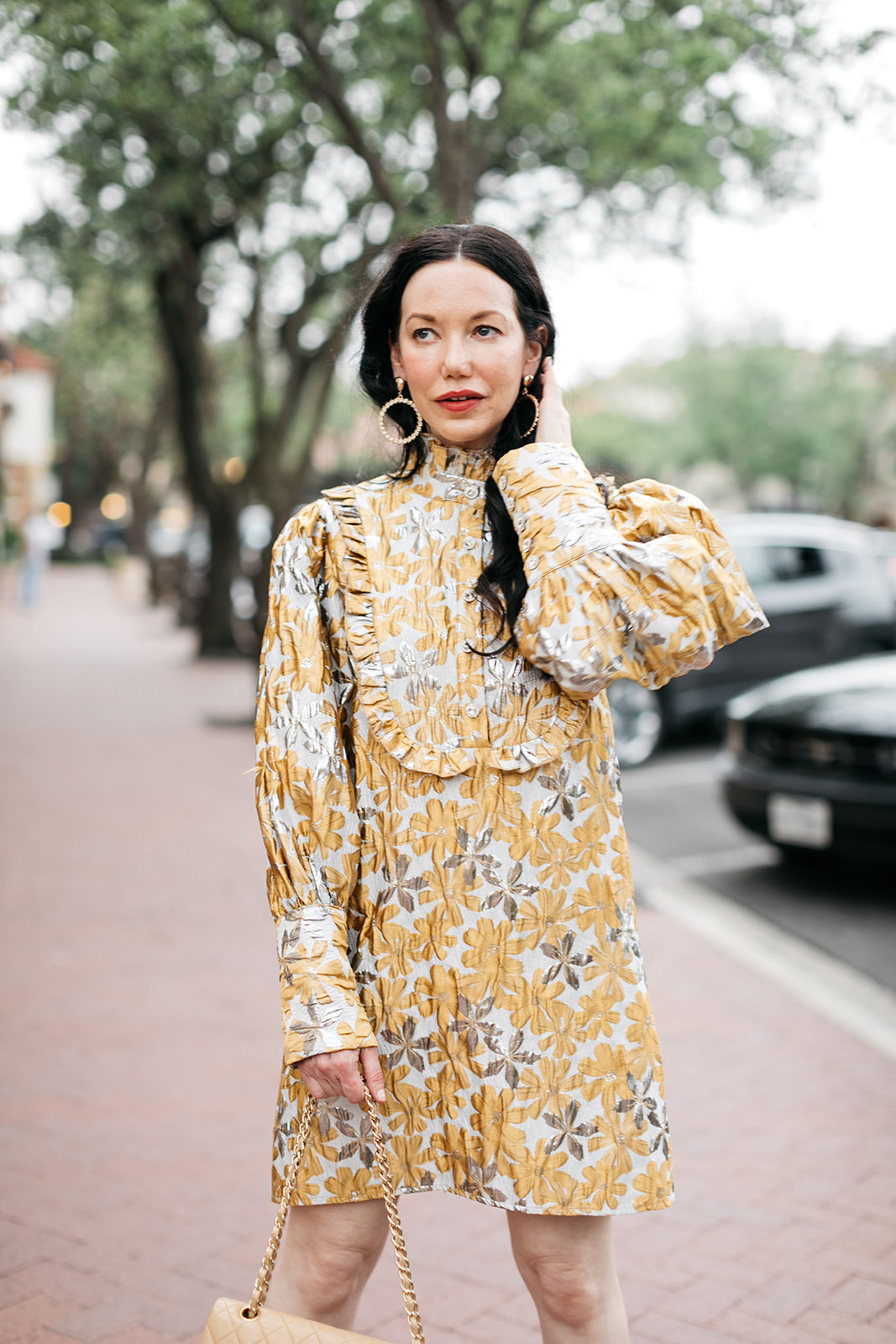 Ettika Gold Plated Statement Earrings, Sister Jane Cocktail Dress   Cocktail Dress by popular Dallas fashion blog, Pretty Little Shoppers: image of a woman walking outside on a brick paved sidewalk and wearing a Sister Jane Cocktail Dress, Chanel Bag, Jimmy Choo Sandals, and Ettika earrings.