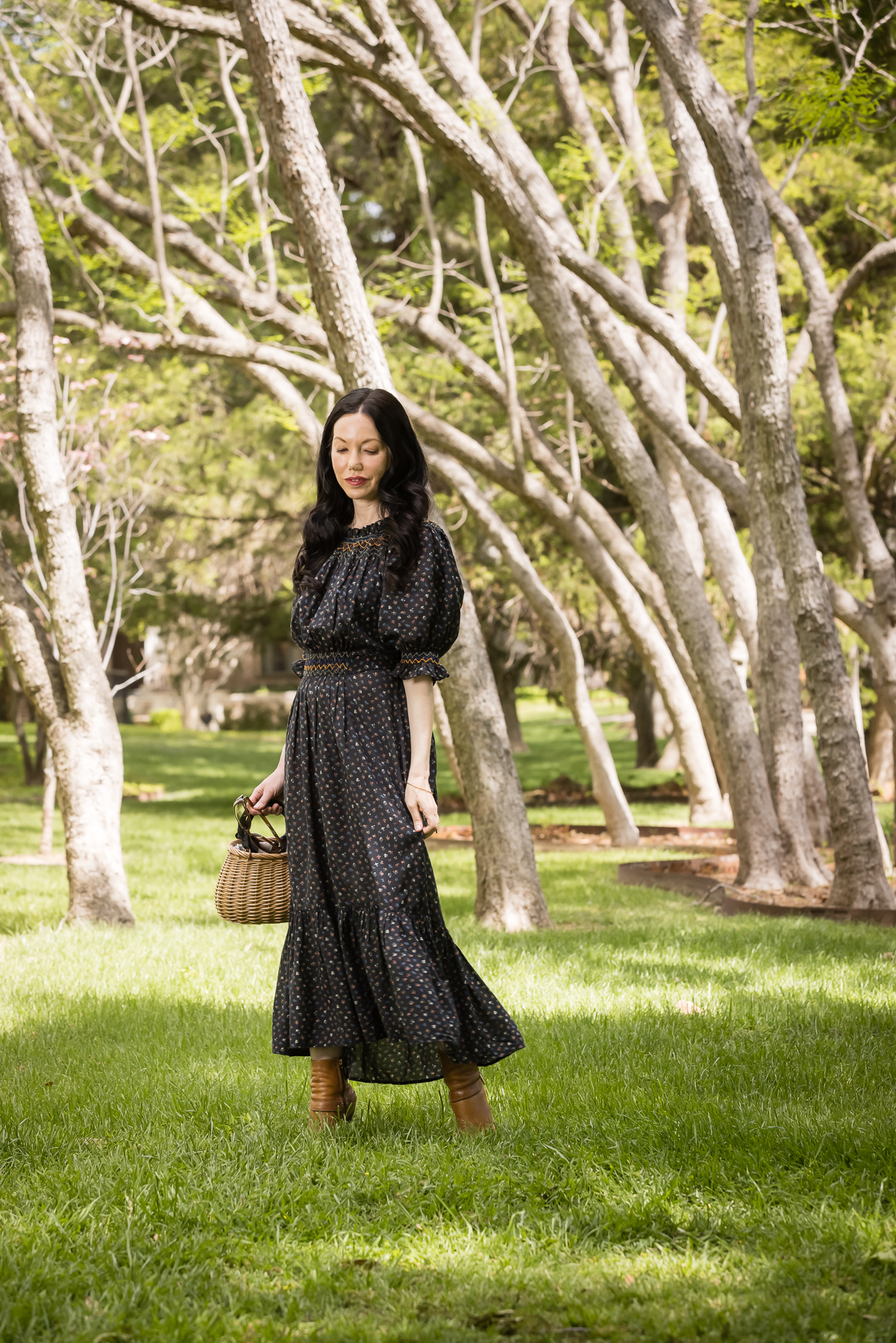 Doen Prairie Dress, Pixie Market Straw Bag, Distressed Ankle Boots | Prairie Dress by popular Dallas fashion blog, Pretty Little Shoppers: image of a woman walking outside on some grass under some trees and wearing a black Down prairie dress, tan boots, and holding a woven handbag