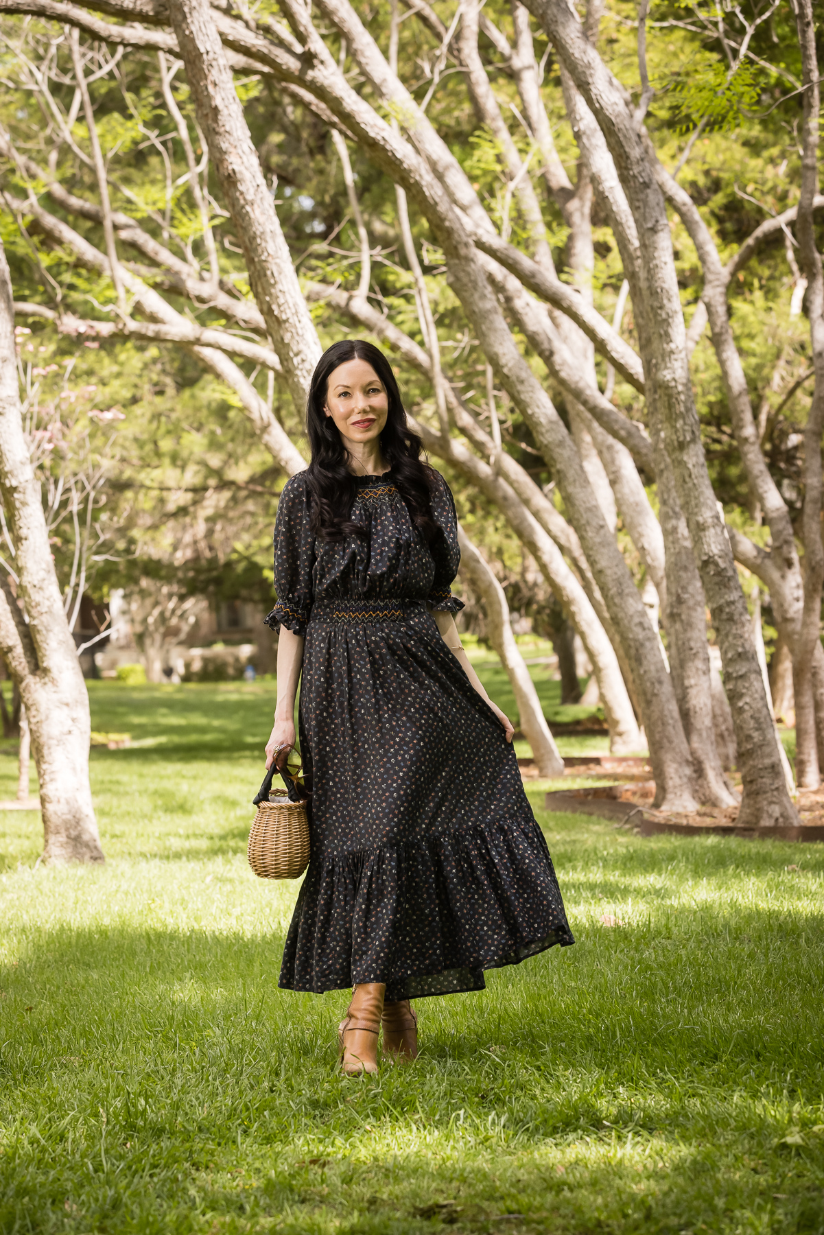 Doen Prairie Dress, Pixie Market Straw Satchel | Prairie Dress by popular Dallas fashion blog, Pretty Little Shoppers: image of a woman walking outside on some grass under some trees and wearing a black Down prairie dress, tan boots, and holding a woven handbag.