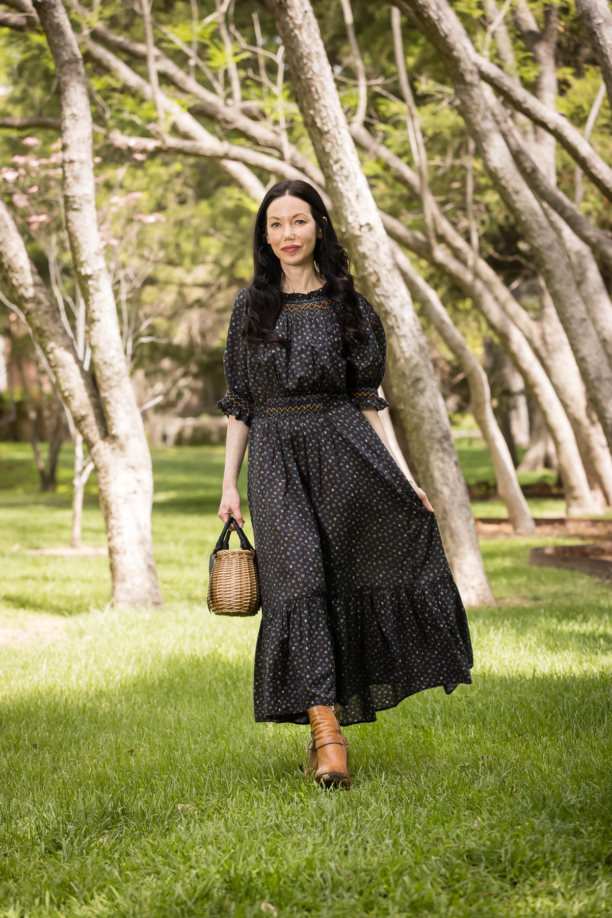 Black Floral Prairie Dress, Straw bag, distressed ankle boots | Prairie Dress by popular Dallas fashion blog, Pretty Little Shoppers: image of a woman walking outside on some grass under some trees and wearing a black Down prairie dress, tan boots, and holding a woven handbag.