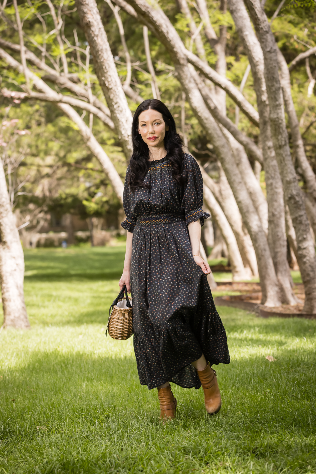 Doen Prairie Dress, Pixie Market Straw Bag, Brown Ankle Boots | Prairie Dress by popular Dallas fashion blog, Pretty Little Shoppers: image of a woman walking outside on some grass under some trees and wearing a black Down prairie dress, tan boots, and holding a woven handbag.