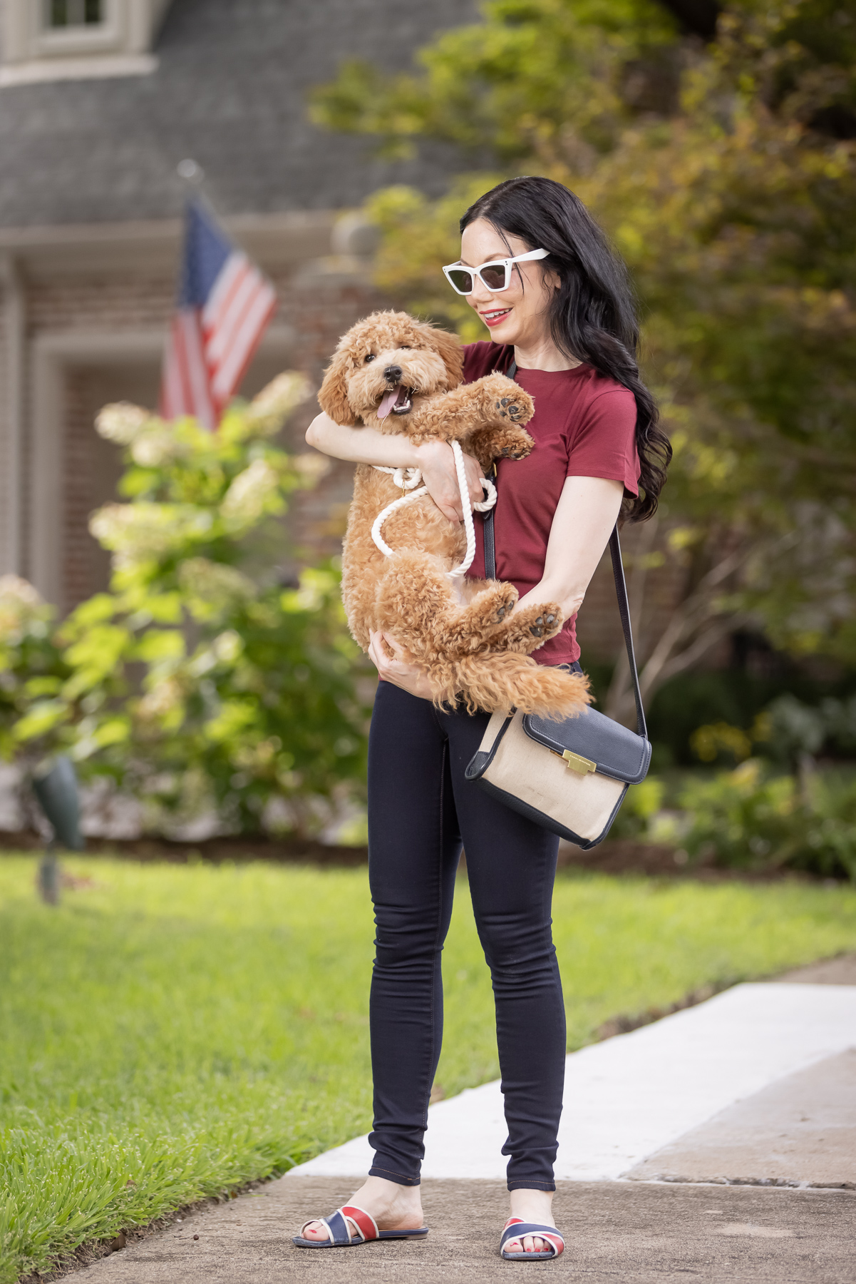 Mott & Bow Jeans and Tee Shirt, Tommy Hilfiger Crossbody Bag, J. Crew Sandals, Italic Cateye Sunglasses, Mini Goldendoodle puppy, Foggy Dog Bowtie, Preppy Style, Dallas Fashion Blogger | Mott and Bow Jeans by popular Dallas fashion blog, Pretty Little Shoppers: image of a woman wearing a crimson t-shirt, Mott and Bow Jeans, blue and red strap slide sandals, and black and tan crossbody bag while standing outside and holding her doodle breed dog.