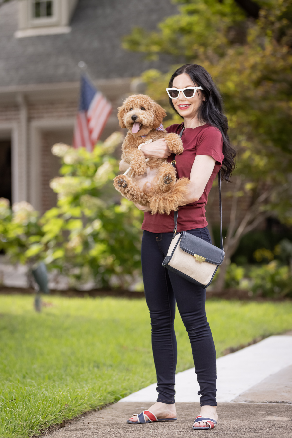 Mott & Bow Jeans and Tee Shirt, Tommy Hilfiger Crossbody Bag, J. Crew Sandals, Italic Cateye Sunglasses, Mini Goldendoodle puppy, Foggy Dog Bowtie, Preppy Style, Dallas Fashion Blogger | Mott and Bow Jeans by popular Dallas fashion blog, Pretty Little Shoppers: image of a woman wearing a crimson t-shirt, Mott and Bow Jeans, blue and red strap slide sandals, and black and tan crossbody bag while holding her doodle breed dog.