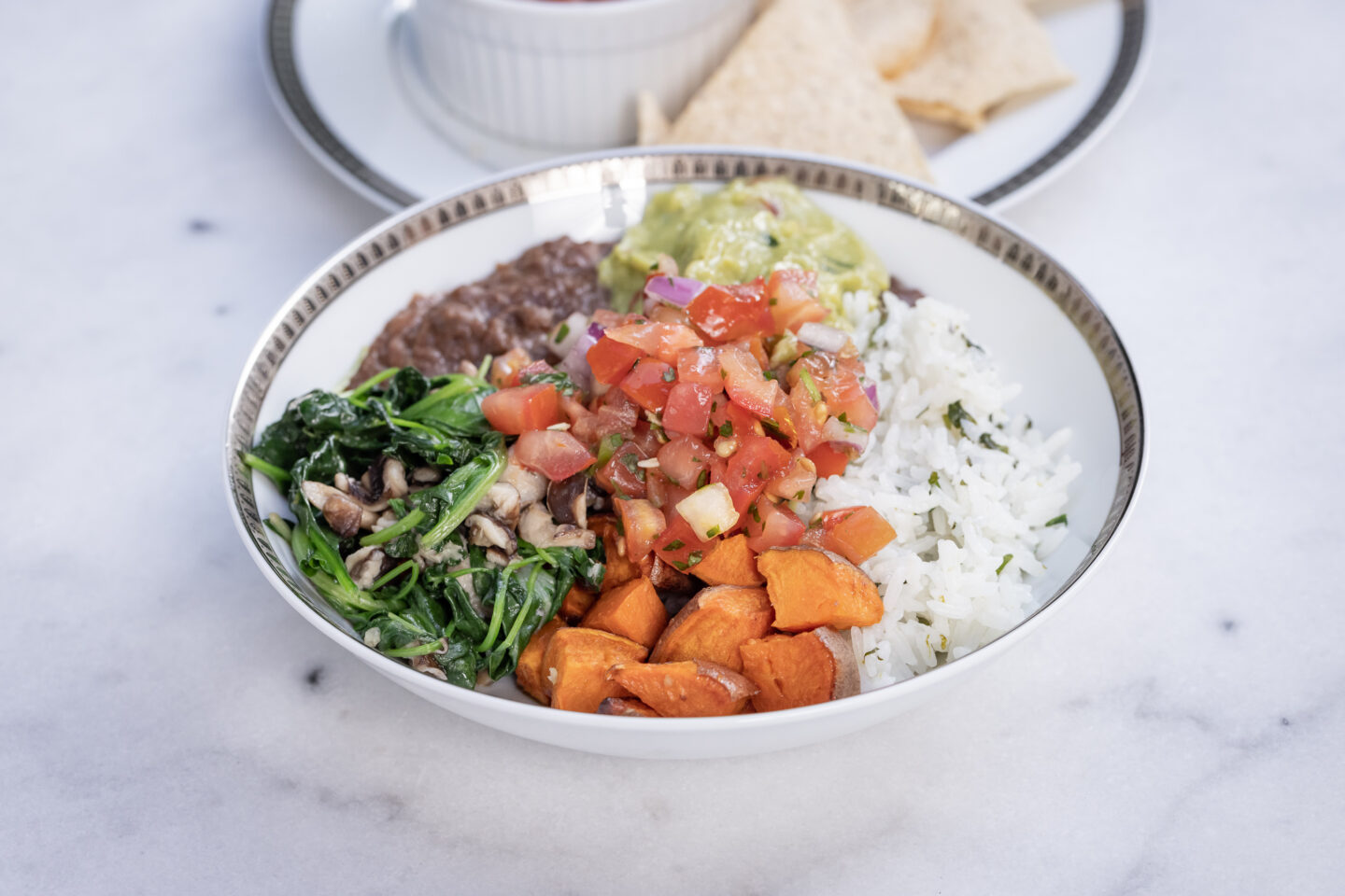 Sweet Potato, Black Bean and Cilantro Lime Rice Burrito Bowl with Sauteed Greens and Mushrooms, Pico de Gallo and Guacamole served with Siete Grain Free Chips and Salsa, Healthy Recipes, Vegan Recipes, Mexican Buddha Bowl, Gluten Free Recipes   Burrito Bowl by popular Dallas lifestyle blog, Pretty Little Shoppers: image of a sweet potato, black bean and cilantro lime rice burrito bowl next to a plate of chips and salsa.