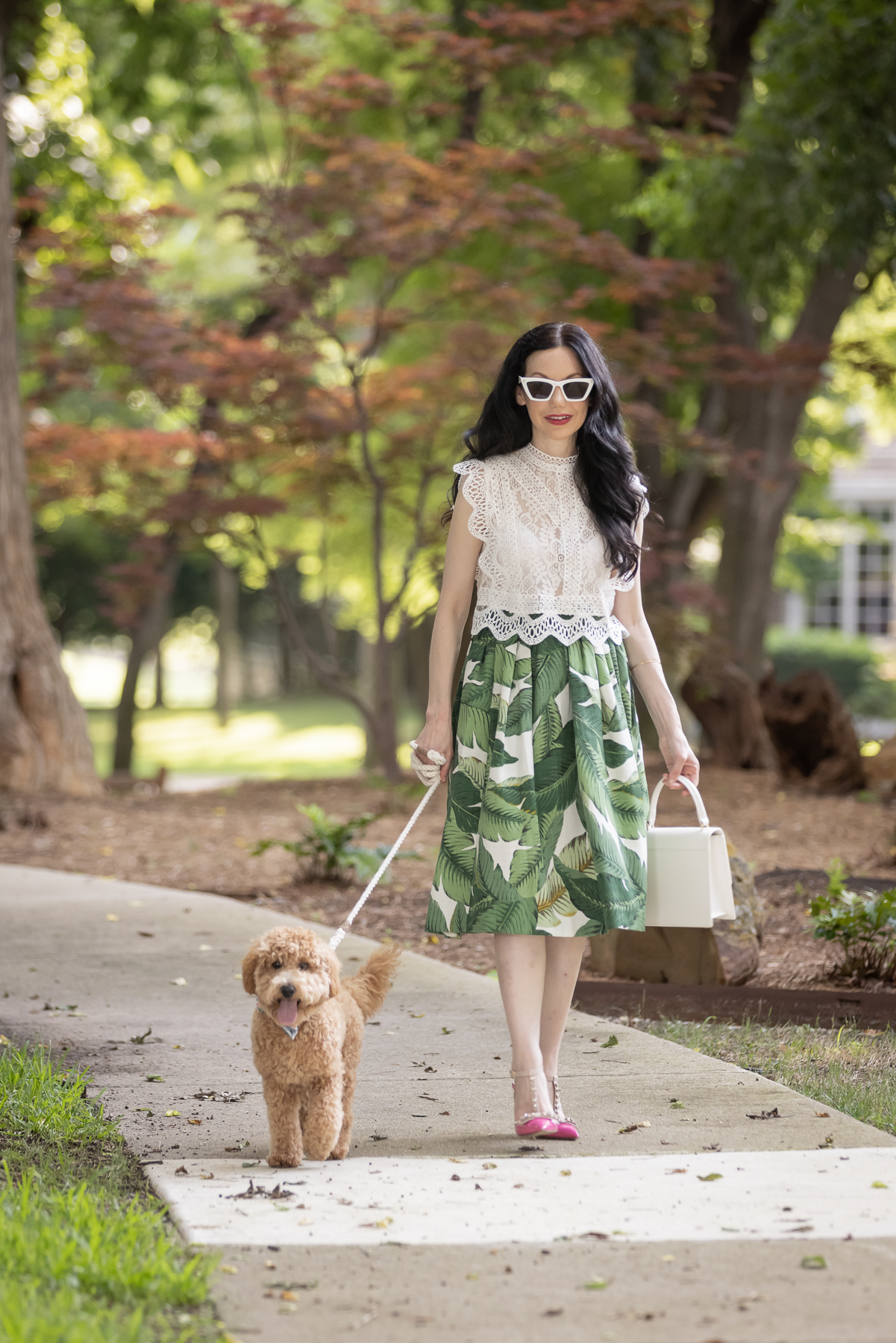 Palm Print Skirt, Neely & Chloe Bag, White Lace Top, Pink Pumps, Fashion Blogger, Fall Transitional Style, Mini Goldendoodle puppy, Fashion Blogger,   Palm Print Skirt by popular Dallas fashion blog, Pretty Little Shoppers: image of a woman walking her dog outside and wearing a palm print skirt, lace cropped top, and pink heels.