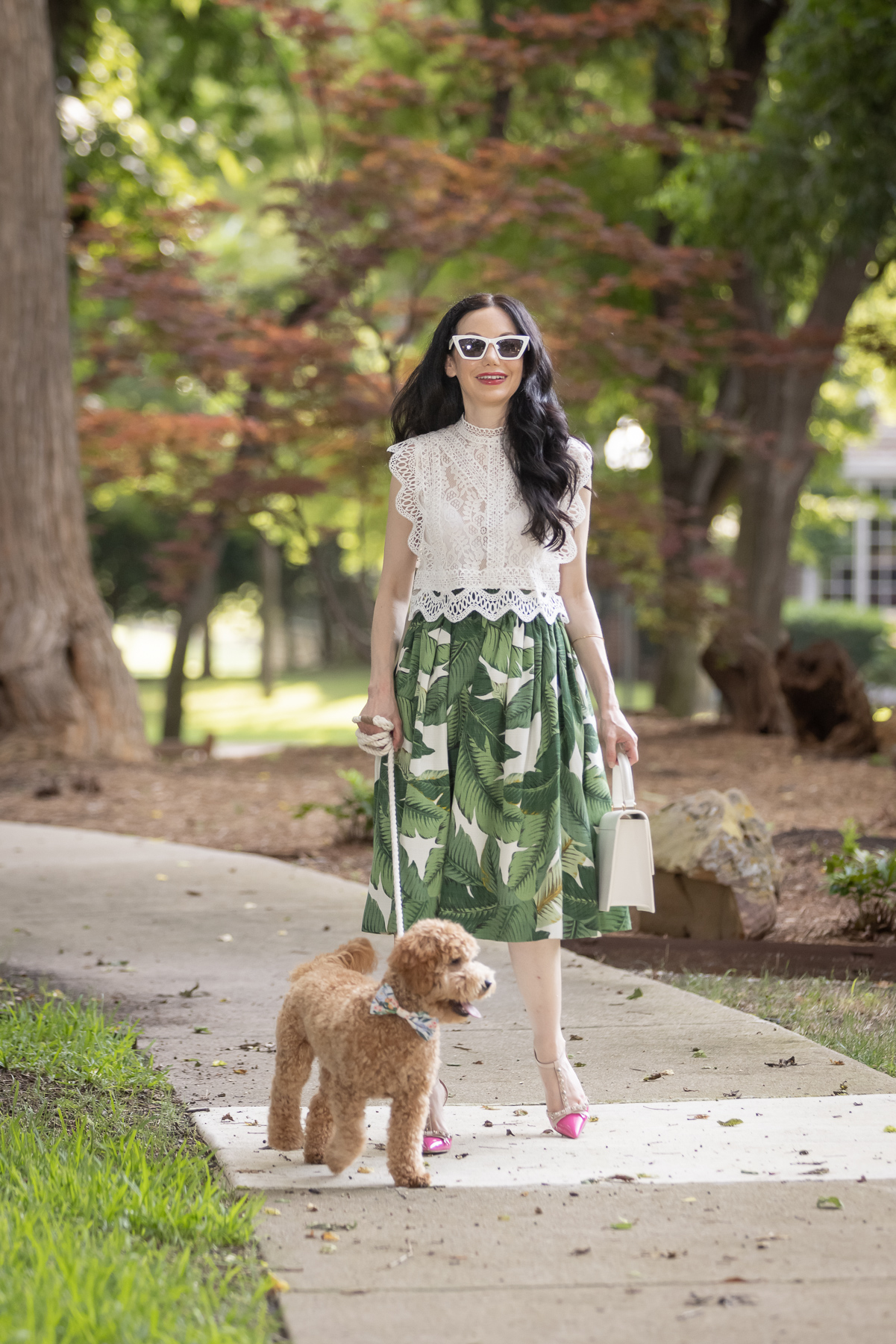 Palm Print Skirt, Neely & Chloe Bag, White Lace Top, Pink Pumps, Fashion Blogger, Fall Transitional Style, Mini Goldendoodle puppy, Fashion Blogger   Palm Print Skirt by popular Dallas fashion blog, Pretty Little Shoppers: image of a woman walking her dog outside and wearing a palm print skirt, lace cropped top, and pink heels.
