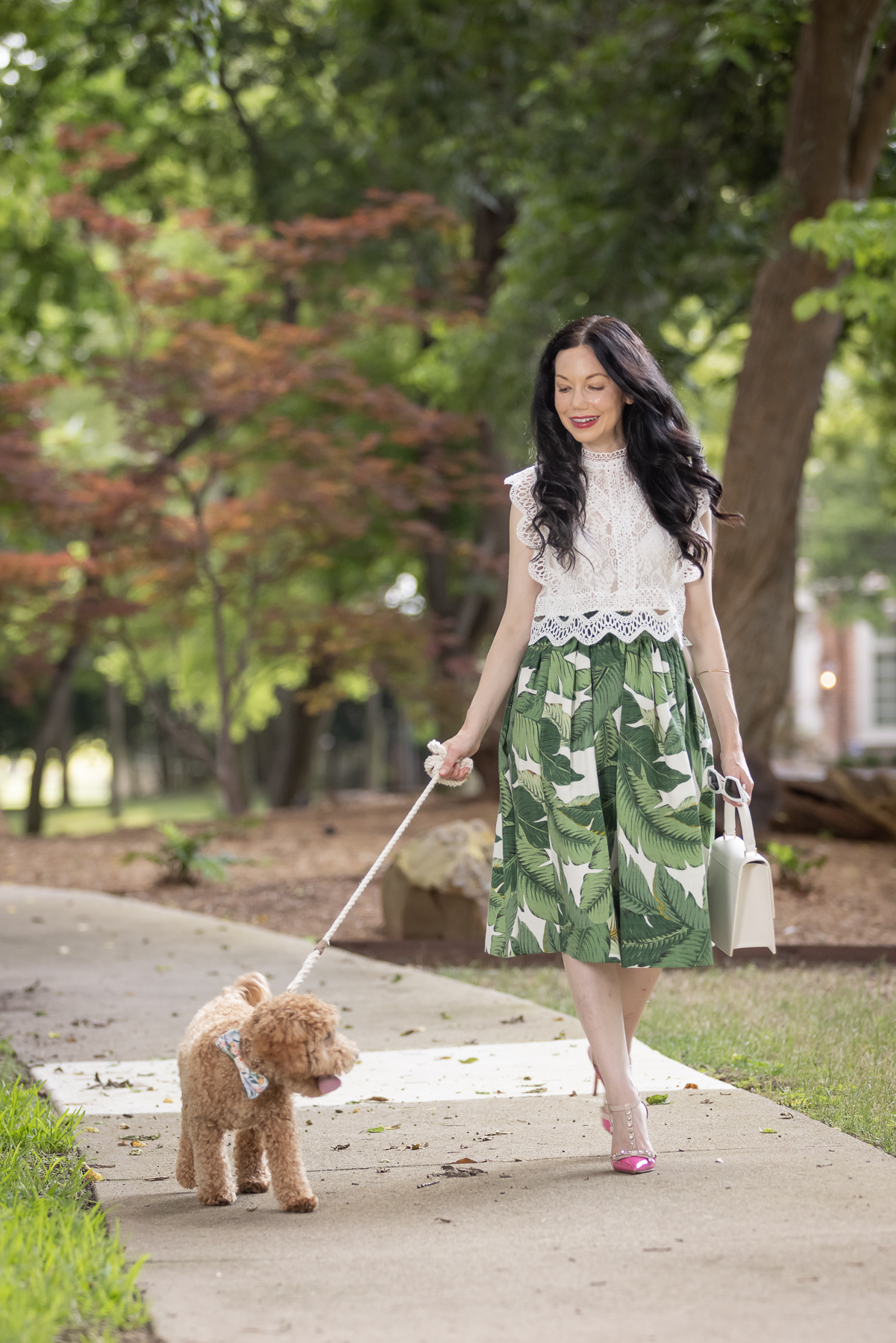 Palm Print Skirt, White Lace Top, Pink Pumps, Mini Goldendoodle Puppy   Palm Print Skirt by popular Dallas fashion blog, Pretty Little Shoppers: image of a woman walking her dog outside and wearing a palm print skirt, lace cropped top, and pink heels.
